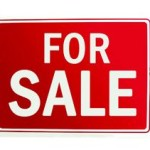 person holding for sale sign